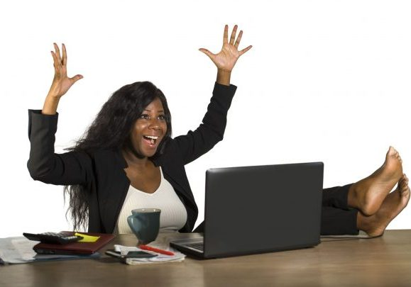 lifestyle office portrait of young happy and attractive black afro American businesswoman working excited with feet on computer desk smiling relaxed celebrating business financial success