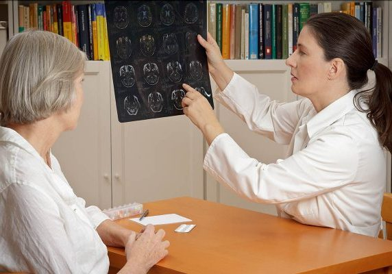 2 women in a  surgery: middle aged doctor in lab coat showing her senior patient magnetic resonance images of her head